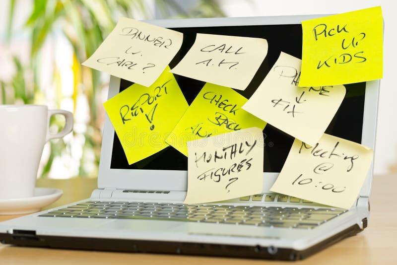 Tela do portátil coberta com as notas pegajosas com nomeações diferentes na mesa de madeira marrom no escritório fotos de stock