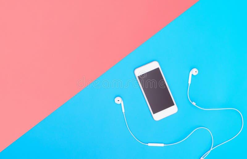 Tela do telefone celular com o fone de ouvido da música no espaço azul da cópia para o cartaz e o texto fotos de stock