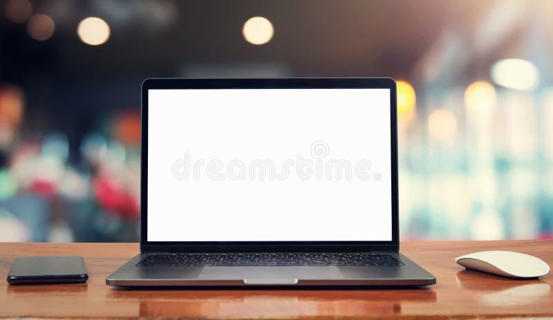 tela e móbil brancos da placa do laptop na tabela no café foto de stock