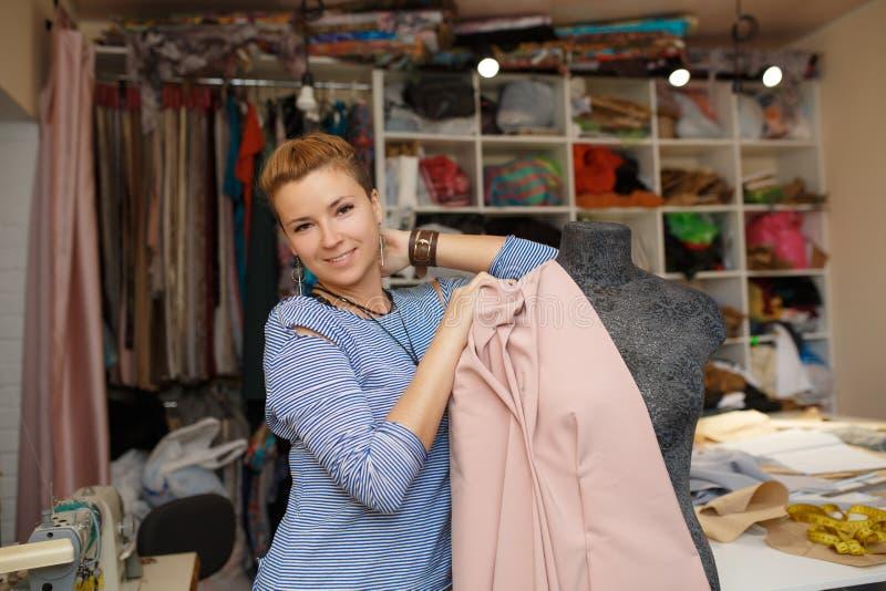 Tela fêmea nova do anexo da costureira ao manequim que usa agulhas criando o projeto do vestido na oficina do alfaiate Indústria  fotos de stock