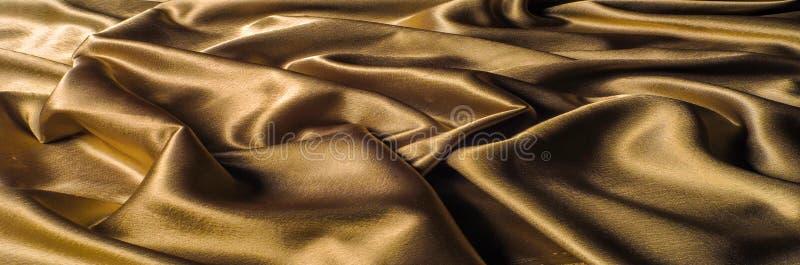 Tela hecha del oro metálico del brillo del hilo del metal de la tela de seda Jus fotos de archivo libres de regalías