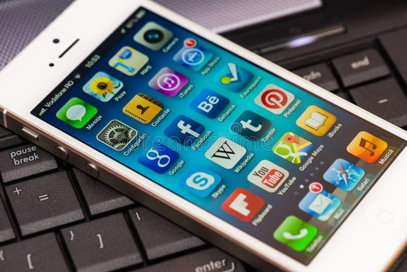 Tela iluminada de Apps do iPhone 5 em um teclado de computador fotografia de stock royalty free