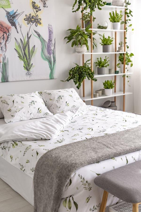 Tela organica bianca e verde e coperta grigia della lana su un letto in una camera da letto luminosa interna in pieno delle piant immagini stock