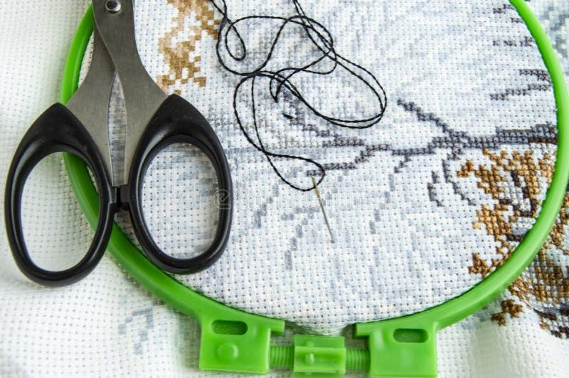 Tela posta piana con un bello modello dei filati cucirini luminosi, delle forbici e di un ago per il primo piano del ricamo immagine stock libera da diritti