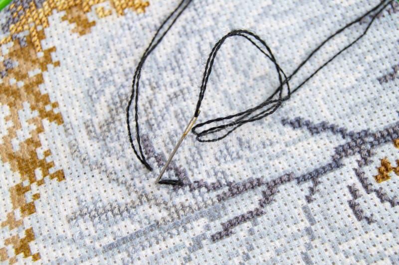 Tela posta piana con un bello modello dei filati cucirini luminosi e un ago per il primo piano del ricamo immagini stock libere da diritti