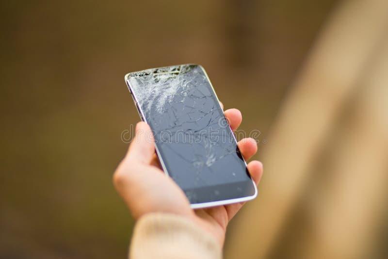 Tela quebrada do smartphone da posse do homem novo Telefone quebrado ? disposi??o fotografia de stock royalty free