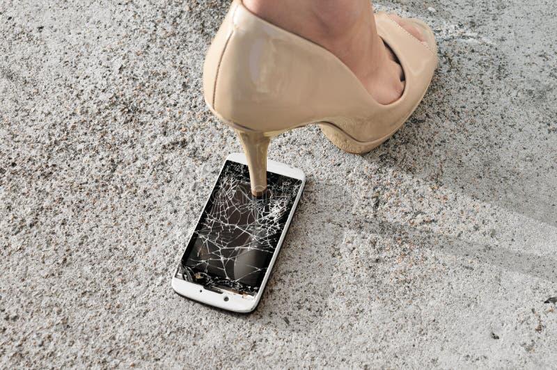 Tela quebrada do telefone do esmagamento pela sapata do salto alto fotografia de stock royalty free