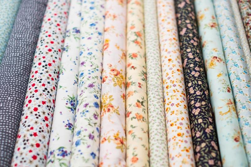 A tela rola com teste padrão floral no mercado de matéria têxtil fotos de stock royalty free