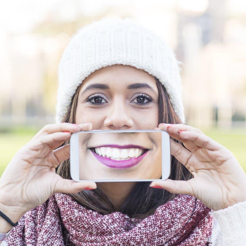 A tela sorrirá vista o telefone, woma da felicidade do retrato do selfie imagens de stock