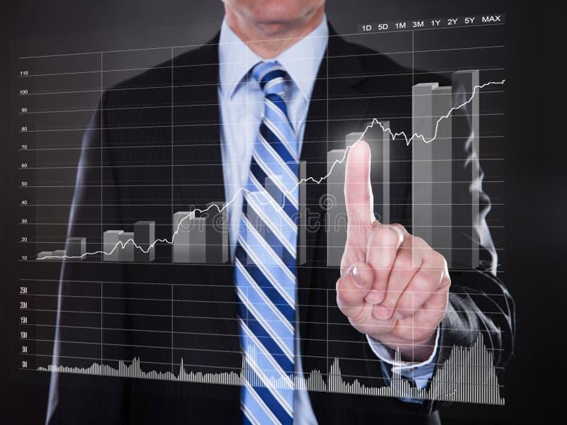 Tela transparente tocante do homem de negócios com gráfico de barra crescente fotos de stock royalty free