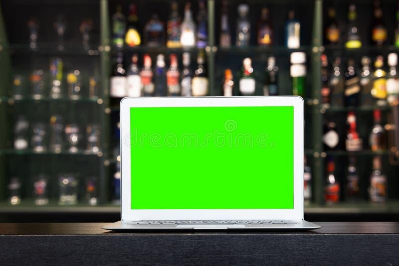Tela vazia do portátil na garrafa da bebida do álcool do borrão no contador da barra no fundo escuro da noite imagens de stock