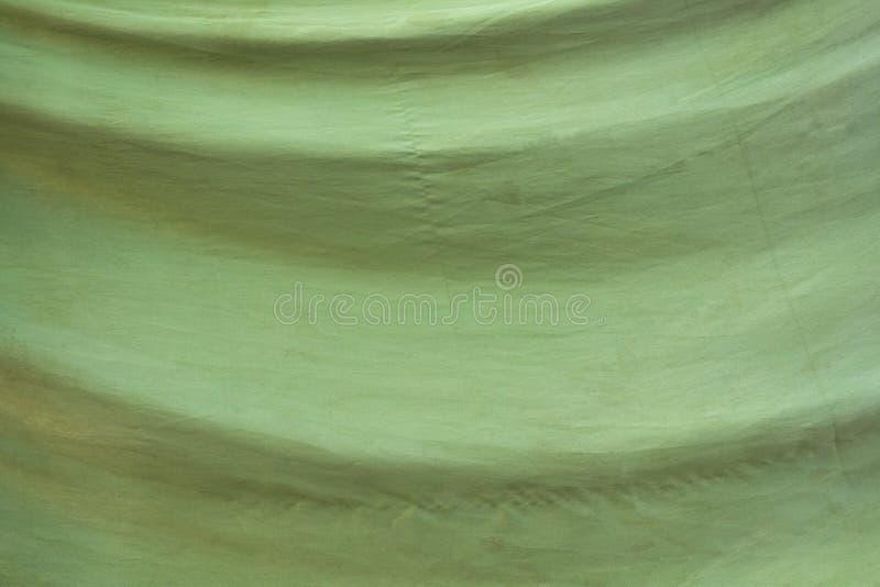 Tela verde desvanecida velha com dobras Textura da superfície áspera fotografia de stock