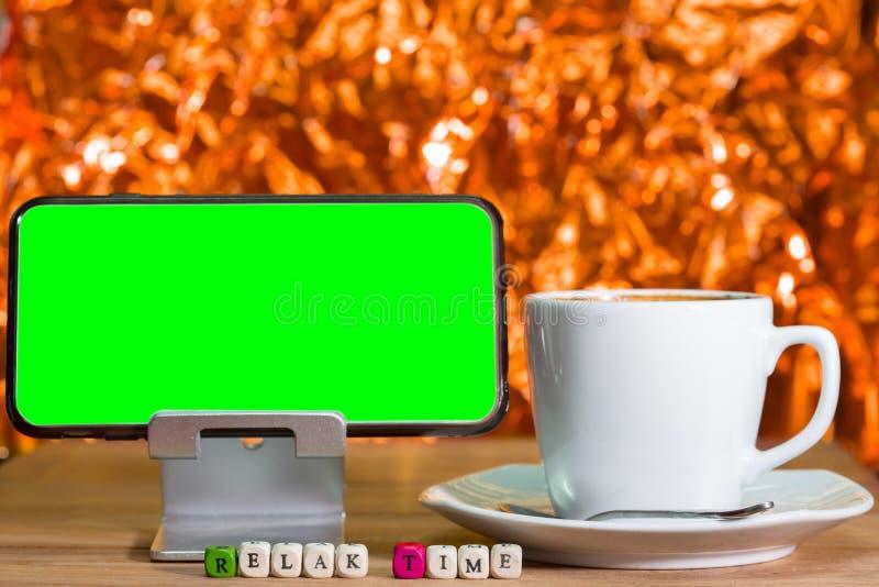 A tela verde vazia no telefone celular e a madeira cortam foto de stock