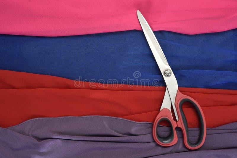 Telas coloreadas cortadas con las tijeras fotografía de archivo libre de regalías