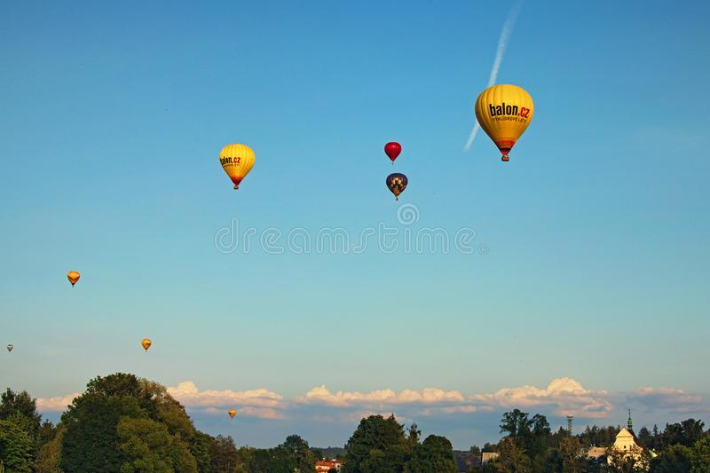 TELC, THE CZECH REPUBLIC-AUGUST 25, 2017: Group flight of hot balloons at sunset over city Telc royalty free stock photography