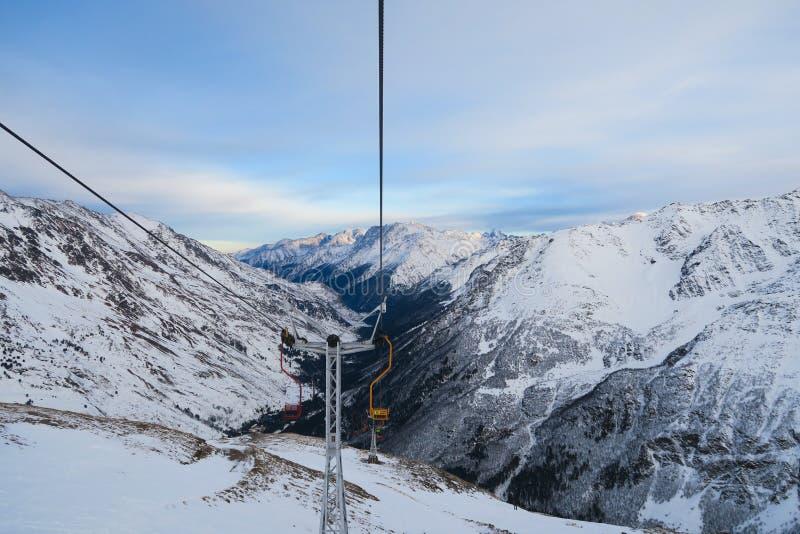 Telecadeira do esqui de Cheget Picos nevados de montanhas caucasianos no céu azul das nuvens imagem de stock