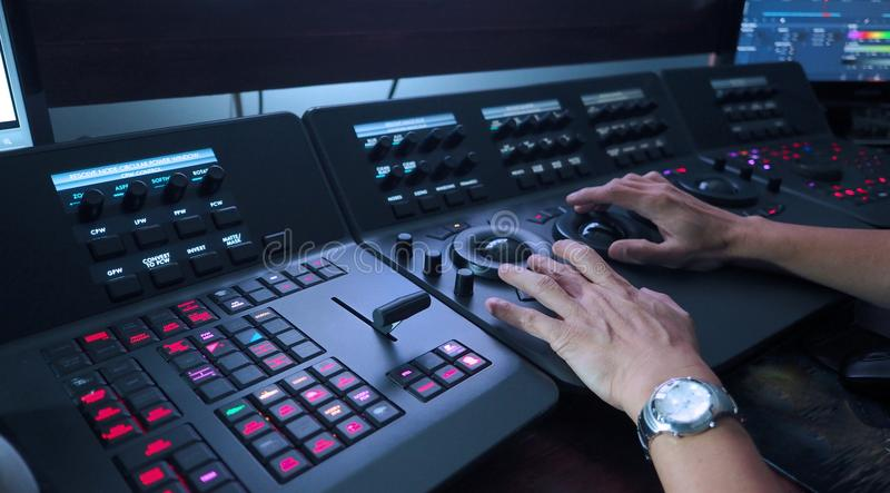 Telecine controller machine and hand editing. Telecine controller machine and man hand editing or adjusting color on digital video movie or film in the post stock photography