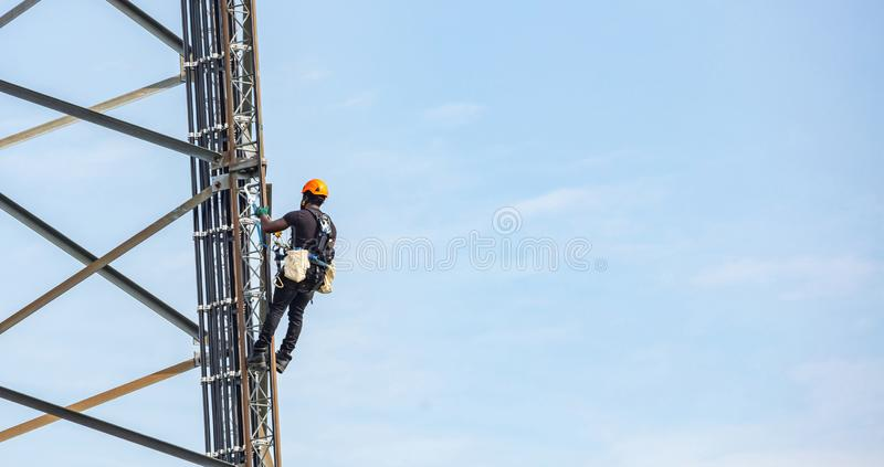 Telecom maintenance. Worker climber on tower against blue sky background stock image