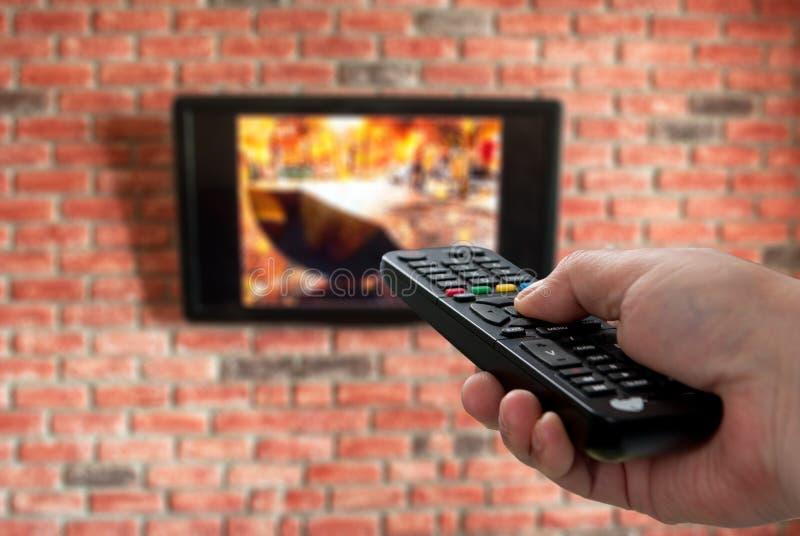 Telecomando della TV a disposizione e muro di mattoni nei precedenti immagine stock