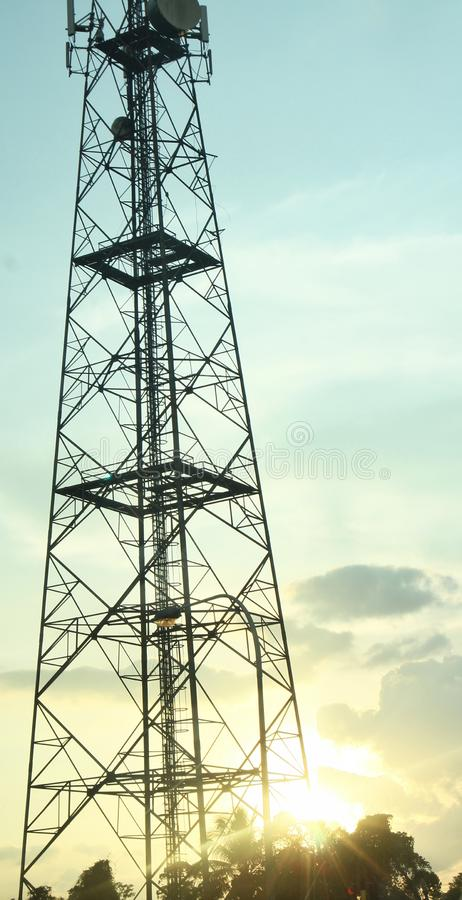 Telecommunicatietoren in karmozijnrode zonsondergang stock foto