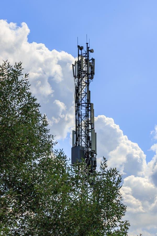 Telecommunicatietoren met elektronisch materiaal op een blauwe hemel met witte wolkenachtergrond tegen groene boom royalty-vrije stock fotografie