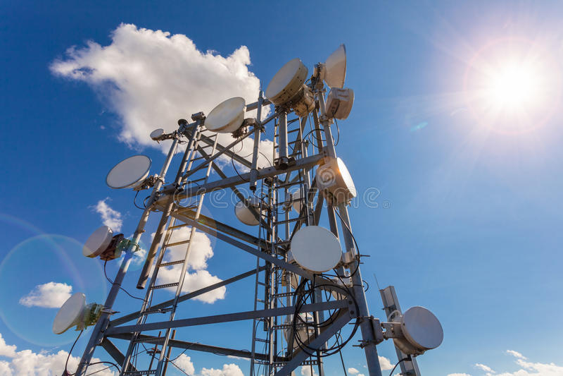 Telecommunicatietoren met TV-antennes, satellietschotel, microgolf en paneelantennes van mobiele exploitant tegen blauwe hemel en stock fotografie