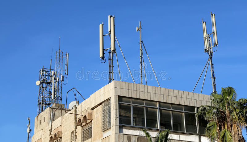 Telecommunication antenna and equipment. On the roof of the building against the blue sky royalty free stock photography