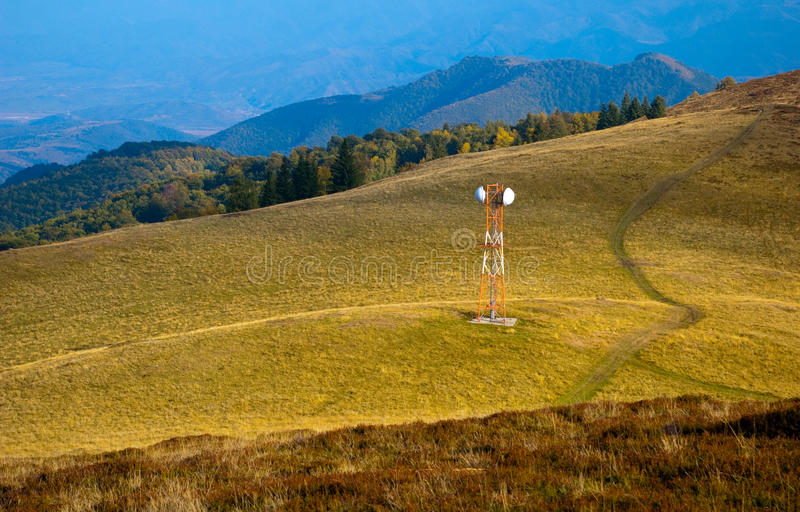 Telecommunication antenna (GSM) on mountain meadow. Pictured in autumn with mountain forest in background stock photo