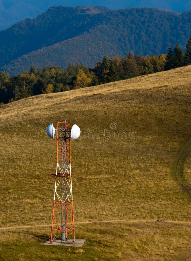 Telecommunication antenna (GSM) on mountain meadow. Pictured in autumn in romanian carpathians stock photos