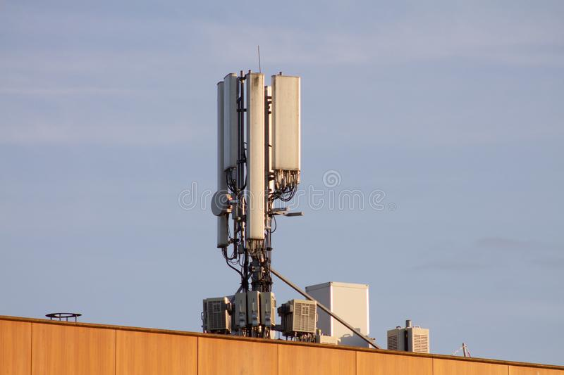 Telecommunication antenna for mobile communication. On a building in a city. Radiator warning for people in surrounding area. GSM on 4g or 5g with this stock image