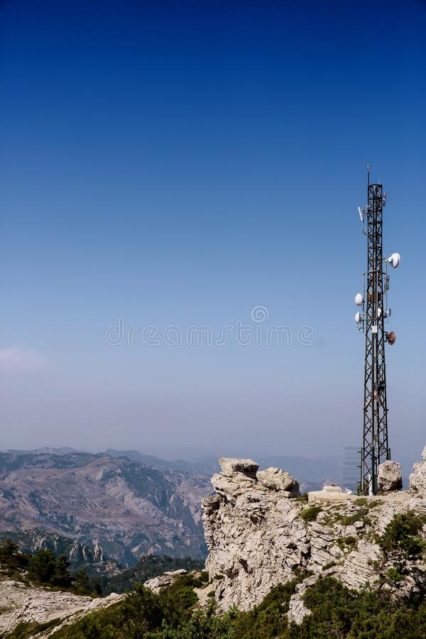 Telecommunication antenna on mountain background. Telecommunication antenna over Tortosa on Caro mount , Spain with mountain background and deep blue sky and stock photography