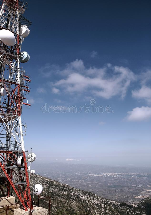 Telecommunication antenna on mountain background. Red and white telecommunication antenna over Tortosa on Caro mount , Spain with mountain background and deep stock photography