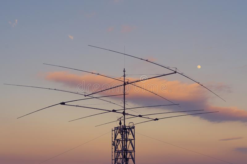 Telecommunication antenna on steel tower and twilight sky in background. Array of telecommunication antennas on steel tower with moon and twilight sky in royalty free stock images