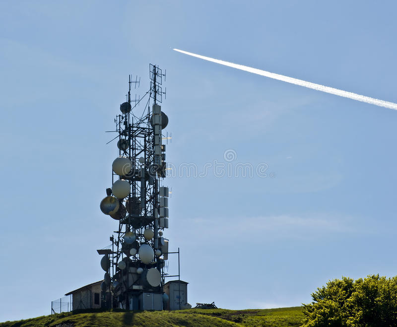 Telecommunication antennas and jet trail. In clear day stock photo