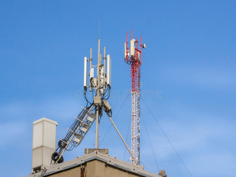 Telecommunication base stations network repeaters on the roof of the building. The cellular communication aerial on a building roof. Cell phone telecommunication stock photography