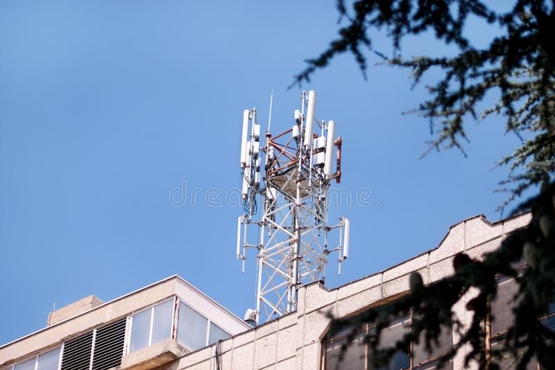 Telecommunication base stations network repeaters on the roof of building. The cellular communication aerial on city building roof stock image
