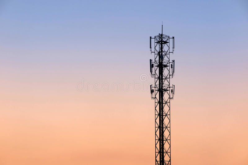 Telecommunication cellular tower. On twilight background. Used to transmit television and telephone signal stock photography