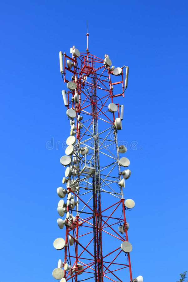 Telecommunication dishes on pylon. Assortment of telecommunication dishes on a pylon against a vibrant blue sky stock photo