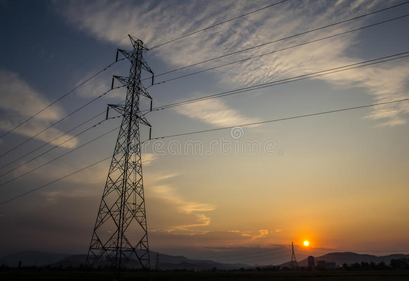 Telecommunication. Electricity transmission pylon silhouetted against blue and orange sky at dusk stock images