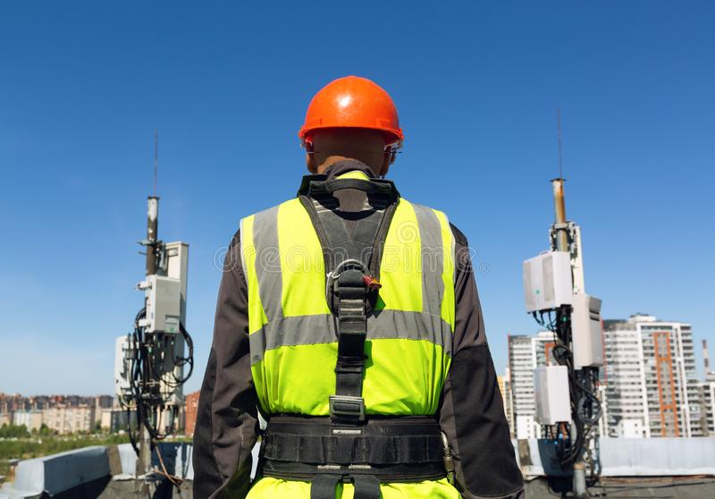 Professional industrial climber in helmet and uniform holds telecomunication equipment in his hand and antennas of GSM stock image