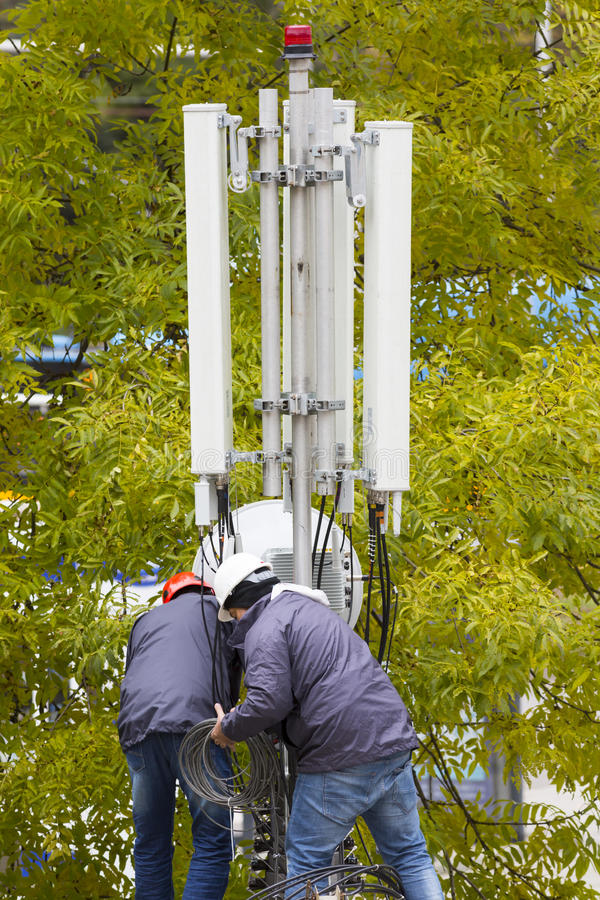 Telecommunication GSM tower workers. Sofia, Bulgaria - October 28, 2016: Workers repair a telecommunication GSM mobile antenna. GSM signal receiver close to the stock image