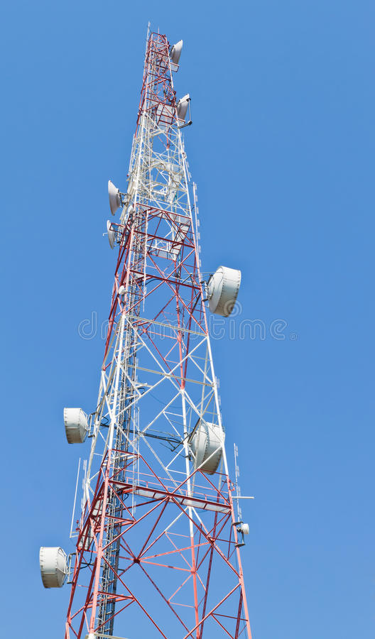 Telecommunication mast. With microwave link and TV transmitter antennas over a blue sky royalty free stock images