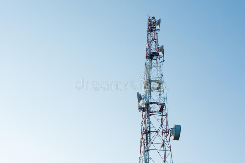 Telecommunication mast with microwave link and TV transmitter an. Tennas on blue sky stock photography
