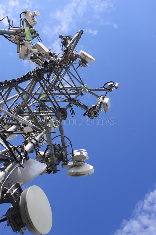 Telecommunication mast. With microwave link and TV transmitter antennas over a blue sky stock image