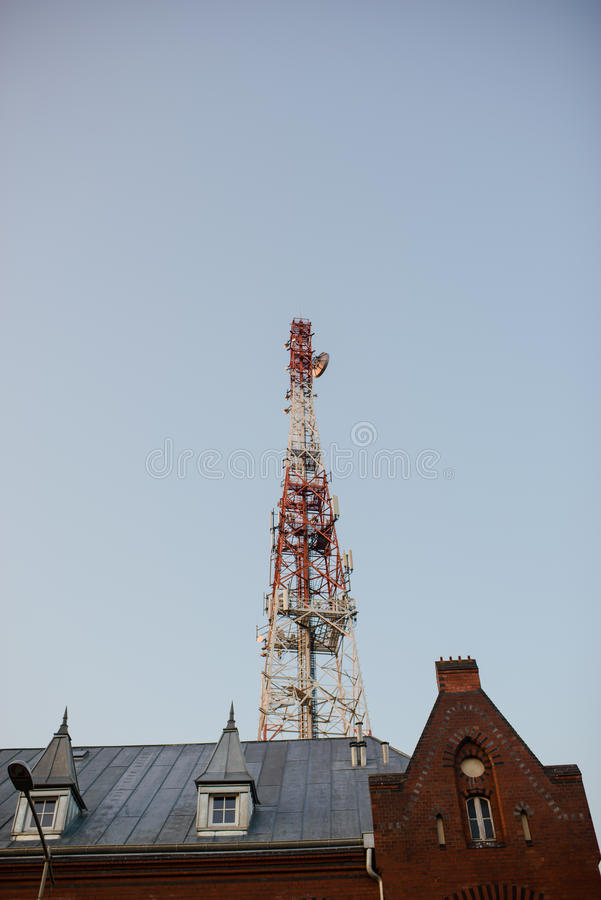 Telecommunication mast TV antennas with blue sky. In the city royalty free stock photo