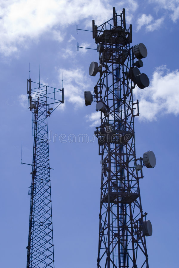 Telecommunication masts2. Two telecommunication masts against a bright blue sky royalty free stock photography