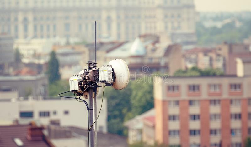Telecommunication microwave antenna dish on a building rooftop with the city in background stock photo