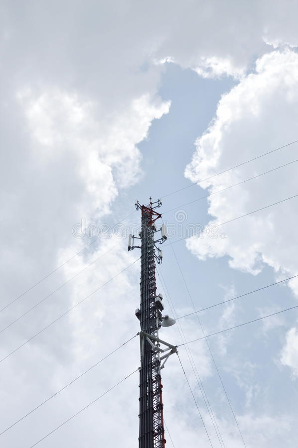 Telecommunication pole on cloud and sky in sunlight royalty free stock photography