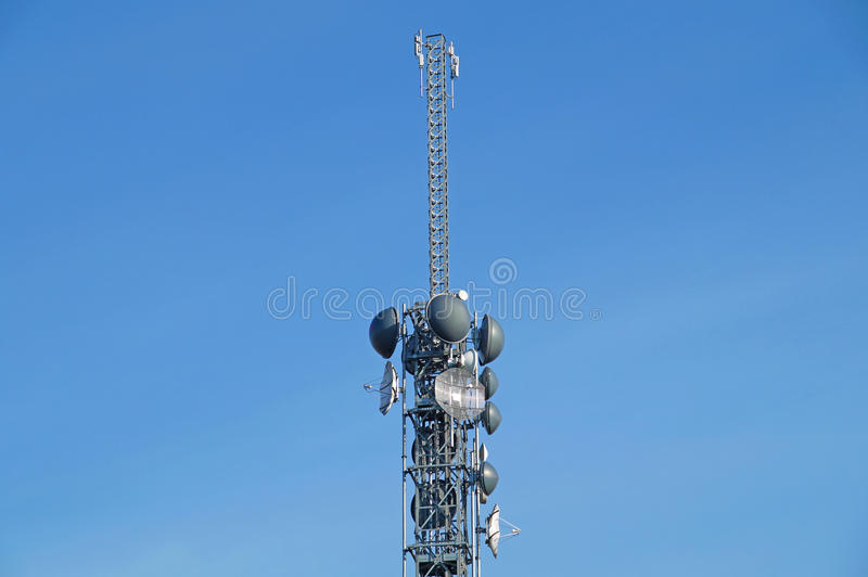 Telecommunication pole tower television antennas with blue sky. Background royalty free stock photos