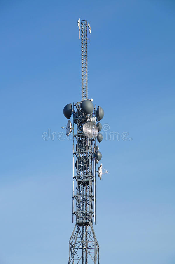 Telecommunication pole tower television antennas with blue sky. Background royalty free stock image